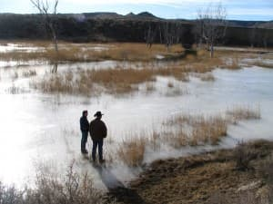 Jill Morrison and Kenny Clabaugh survey an ephemeral draw flooded and frozen with coal-bed methane water on a Campbell County ranch in 2006. (Dustin Bleizeffer/WyoFile — click to enlarge)