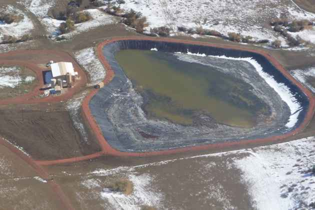 Coal-bed methane gas activity in the Powder River Basin is depicted by new road and pipeline installations in this 2002 file photo. Thousands of wells and related facilities have been orphaned, leaving a cleanup liability in the tens of millions of dollars. (Photo courtesy of Powder River Basin Resource Council — click to enlarge)