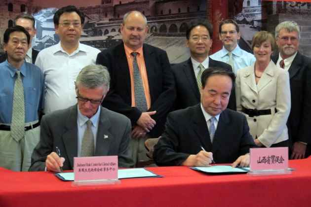 David Wendt, president of the Jackson Hole Center for Global Affairs (left) and Chairman Yuan of Shanxi Provincial Peoples' Congress sign a memorandum of understanding to continue to work together to strengthen partnerships between the two entities. (Dustin Bleizeffer/WyoFile — click to enlarge)