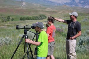 Draper Museum Research Assistant Nathan Horton pointing out a Golden Eagle nest to young participants in the Center of the West's Eyes on Eagles Discovery Camp.  (Photo by C. Preston - click to enlarge)