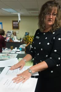 Teton County Clerk Sherry Daigle explains the differences between old and new marriage license applications, licenses, and certificates in Jackson on Tuesday. Although the county has the highest per-capita marriage rate in the state, the Teton Mountains being a destination site for weddings, no same-sex couples sought licenses in the first two hours same-sex marriage became legal. (WyoFile/Angus Thuermer Jr. — click to enlarge)