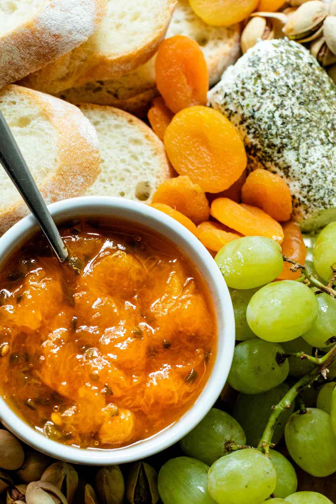 Top down view of peach jalapeño jam with a spoon in a white bowl surrounded by grapes, bread, dried apricots, cheese and goat cheese on a brown serving board