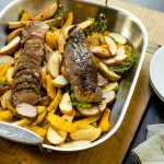 Roasted pork tenderloin sitting on bed of apples and squash in a roasting pan on a wood board with white plate and silverware on a gray slate surface
