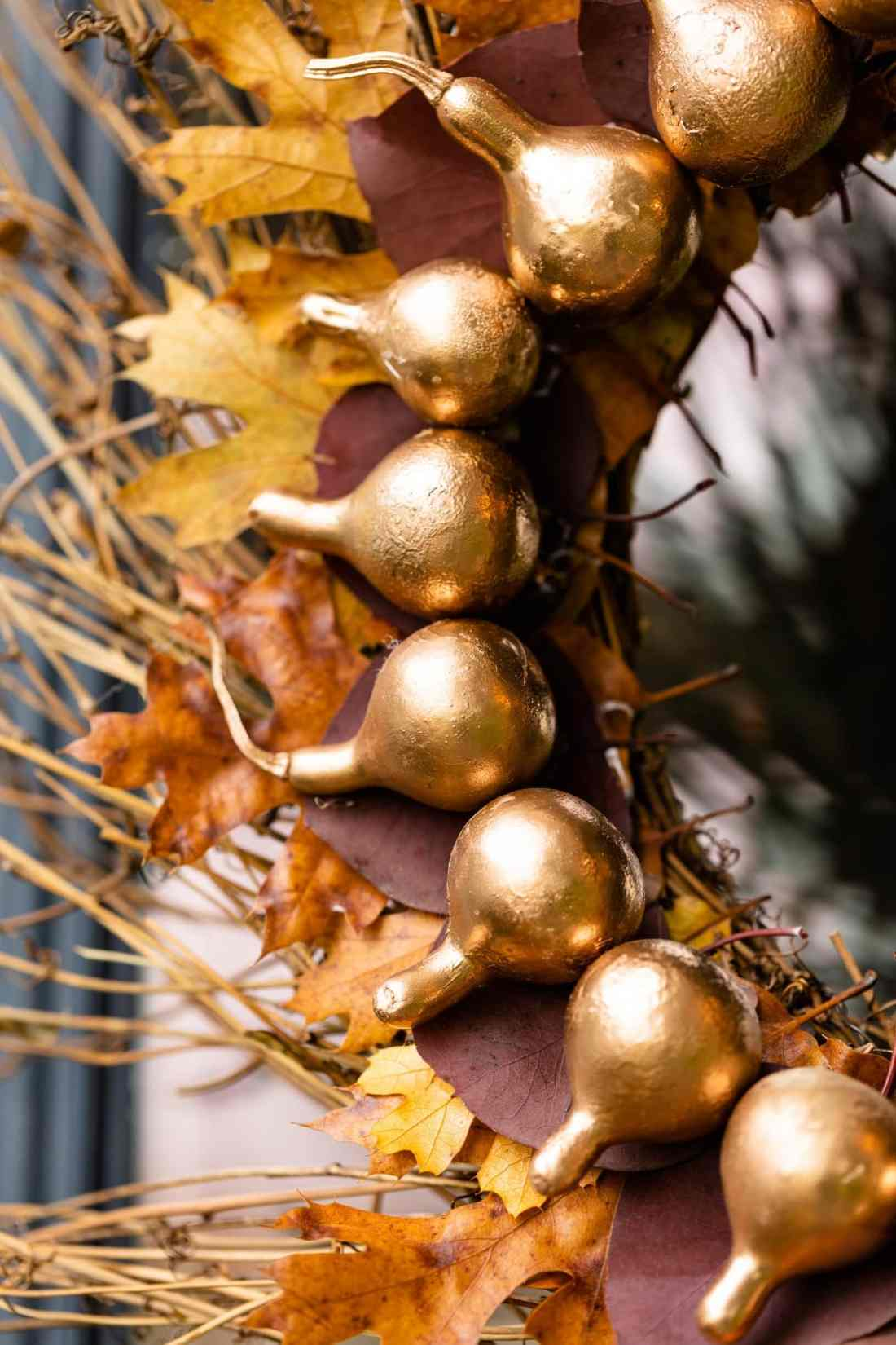 Close view of dried gourds spray painted gold with petrified leaves behind on a grapevine DIY fall wreath