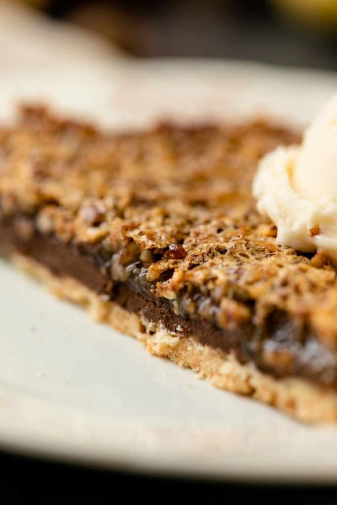 Pecan pie bars sitting on white plate with scoop of vanilla ice cream on top all on gray slate surface