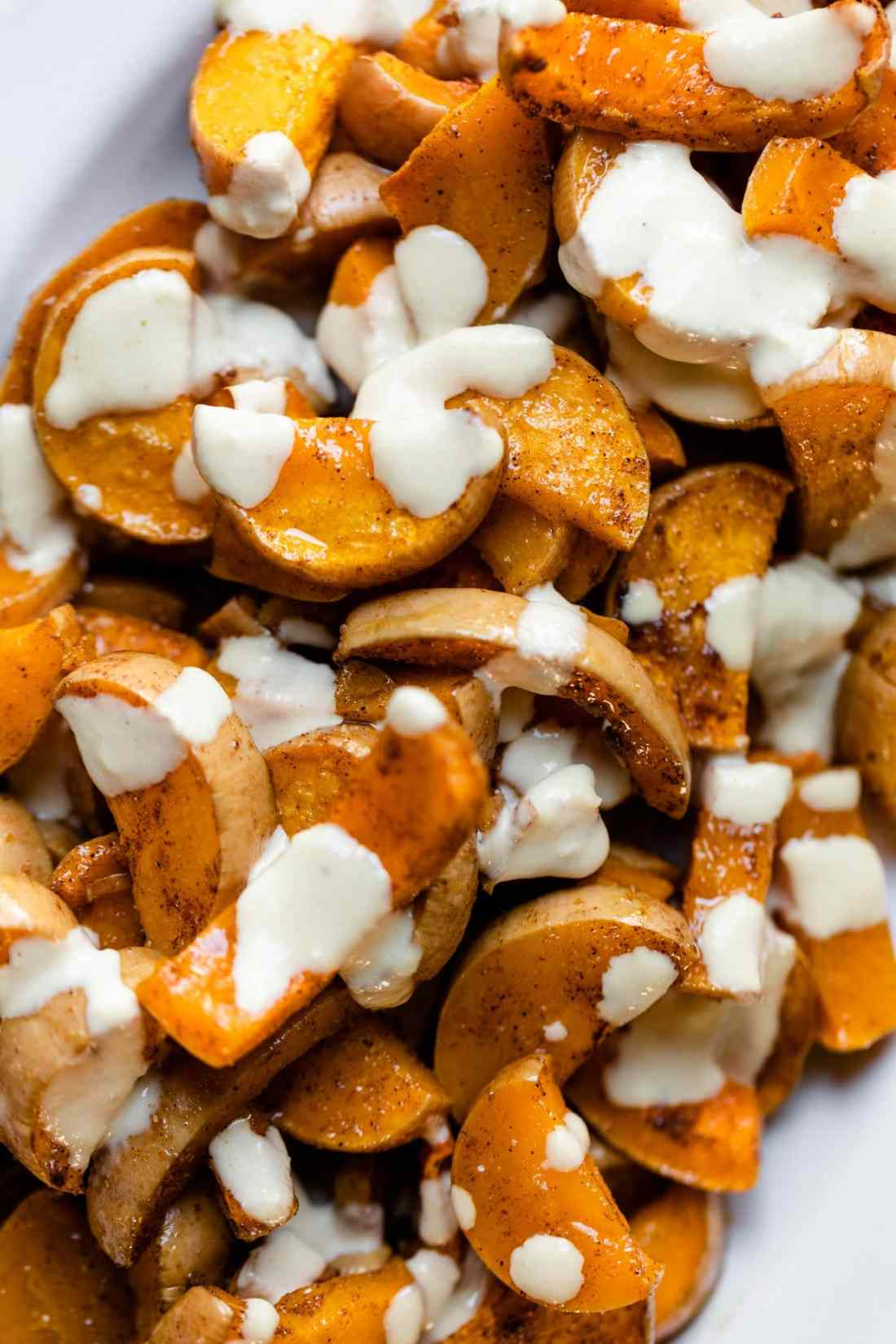 Spiced butternut squash drizzled with white tahini sauce sitting on white platter