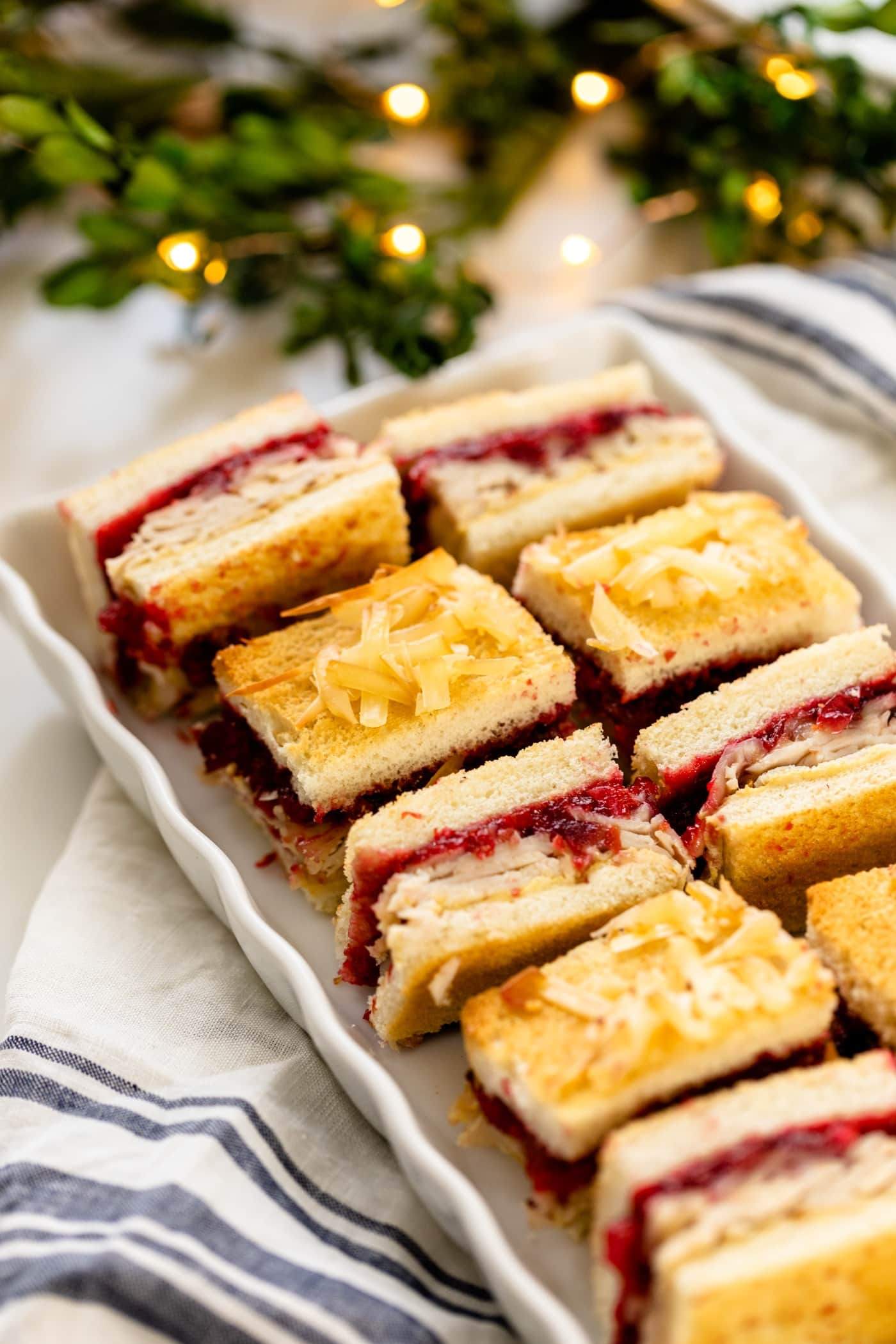 Turkey cranberry croque monsieur sandwiches sitting on white serving plate with linen napkin underneath with Christmas lights and greenery in background on white surface
