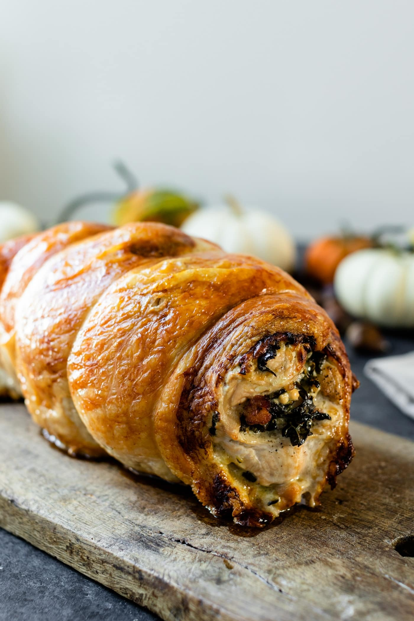 Turkey roulade sitting on wood board with pumpkins and gourds in background on a gray slate surface