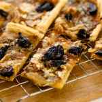 Pieces of caramelized onion tart topped with dried figs and blue cheese sitting on cooling rack on wood board all on white surface