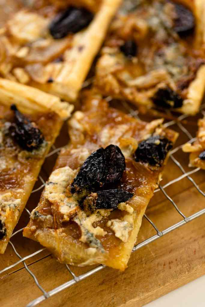 Caramelized onion tart topped with dried figs and blue cheese sitting on wire rack on wood surface