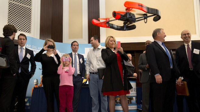 Lucy Malin, 8, of Arlington, Va., in pink, watches as a Parrot Bebop drone flies_27997