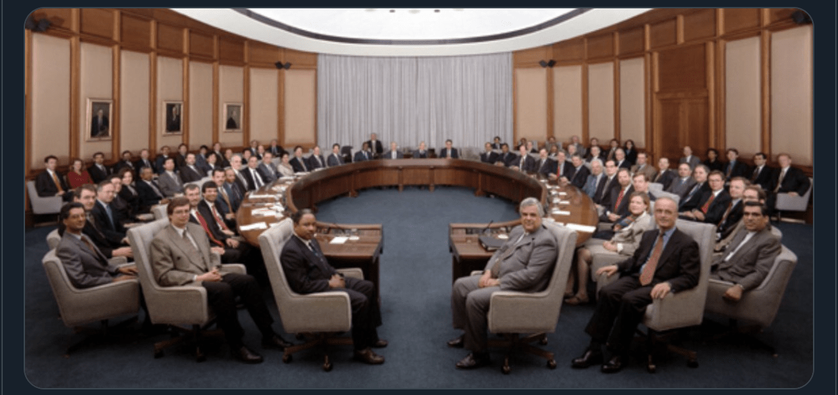 Large conference room filled with dozens of middle aged white men captioned Oracle Board Deciding Next TikTok Feature