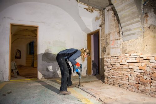 woman drilling the basement floor | Xcellence Inspection Services | Bathroom in the basement Chicago