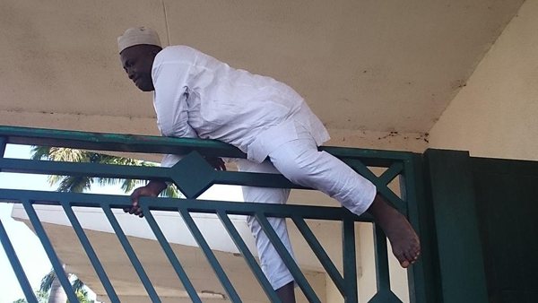 Hon Cheche, from Niger State, climbing over NASS gate to enter the premises