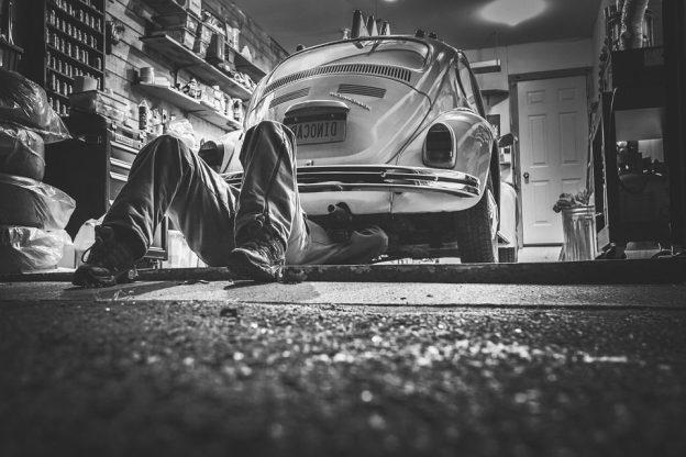 man doing repair on his beetle car