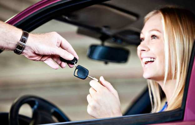 smiling girl receiving car keys from a man