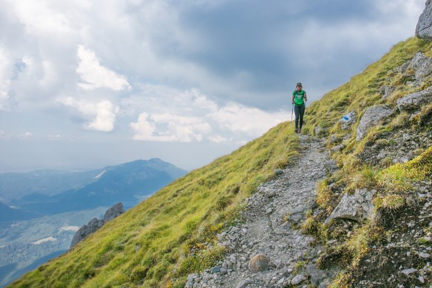 איזה מטיילת על הר גבוה וירוק ברקע עננים והרים אחרים וגאיות