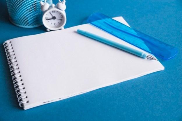 בלוק כתיבה עם סרגל, שעון ועט ופח