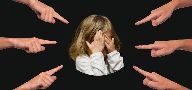 ילדה עצובה שמצביעים עליה