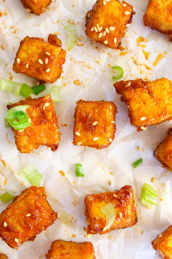 crispy and spicy honey garlic tofu close up on a white background