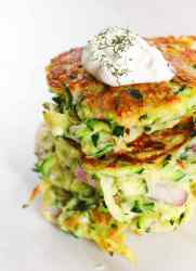 zucchini fritters with feta, red onion, and dill topped with sour cream on a white background