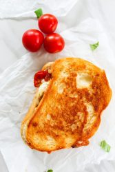 a whipped feta grilled cheese with cherry tomatoes on a white background