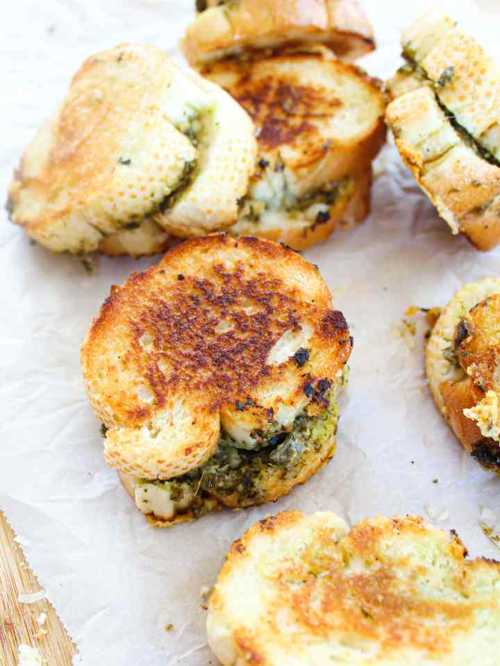 easy mini grilled cheese sandwiches with pesto and shredded white cheddar on a white parchment background