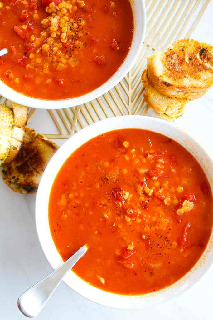 two bowls of smoky tomato lentil soup with small grilled cheese sandwiches