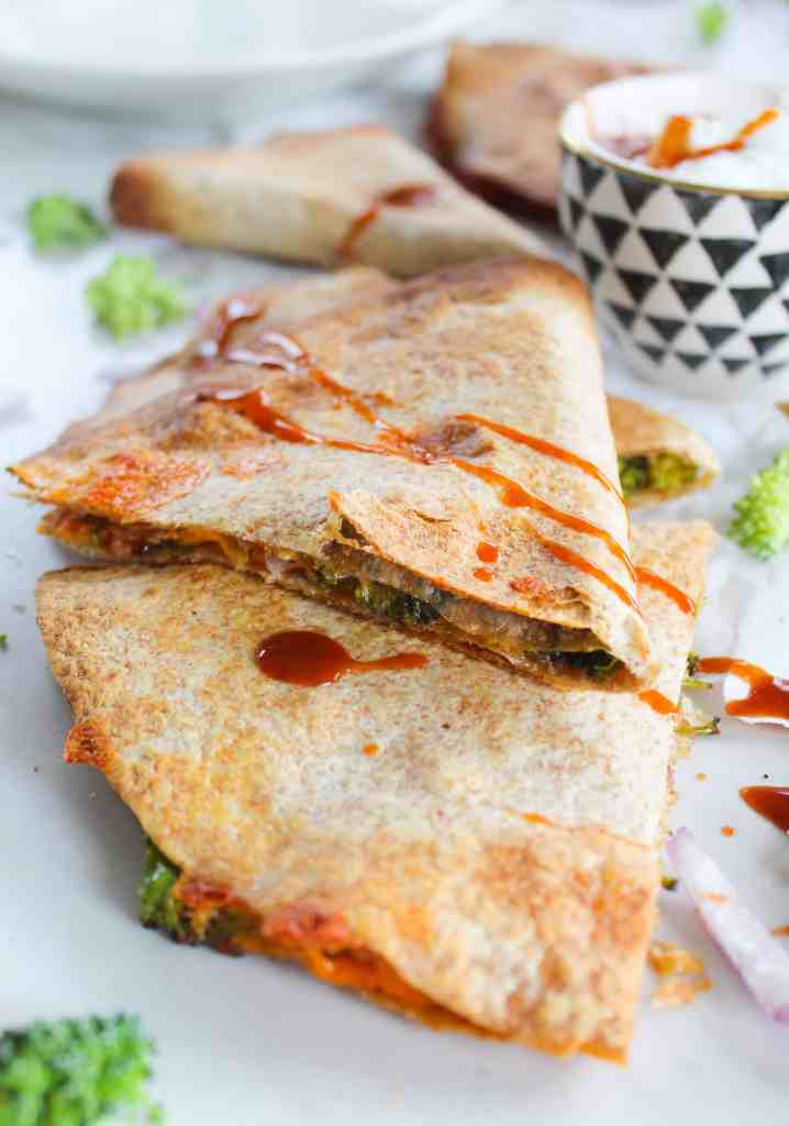 crispy oven baked quesadillas with broccoli and cheddar on a white background