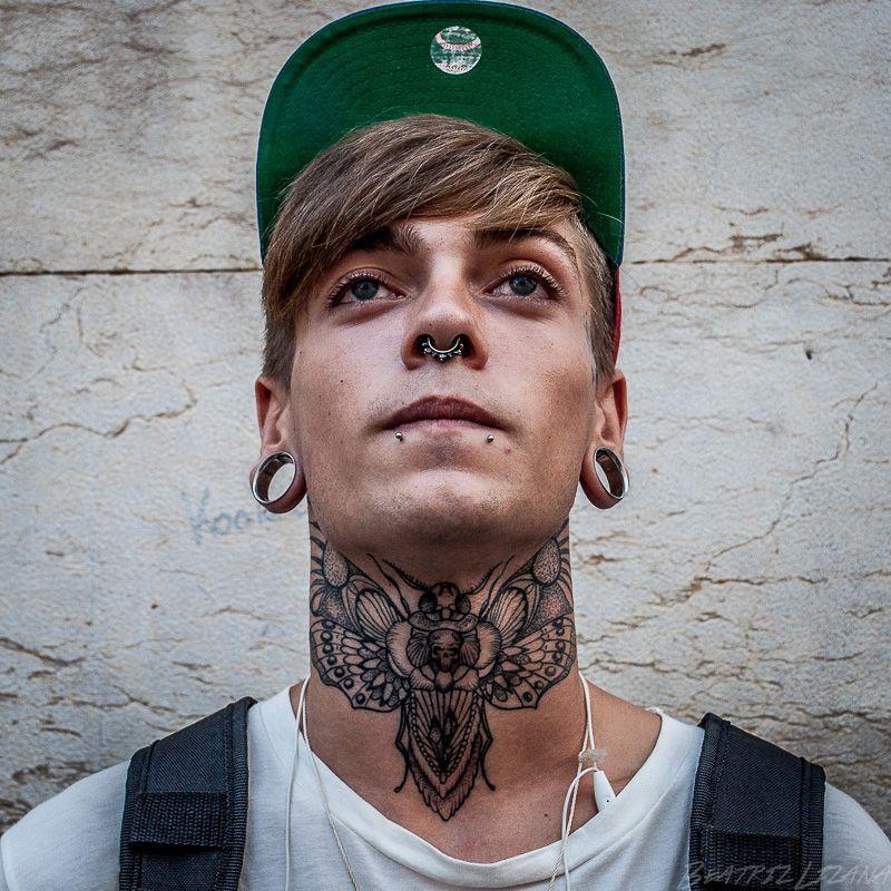 retrato de Óscar con un tatoo de una mariposa enorme en el cuello