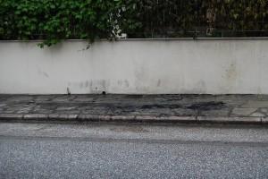 Το σημείο που ήταν το παρκαρισμένο αυτοκίνητο, με τα αποκαϊδια του εμπρησμού. Τα καμμένο αυτοκίνητο είναι στα χέρια της αστυνομίας.