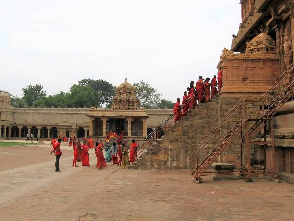 Tanjore pélerins habillés en rouge qui montent un escalier sur un temple