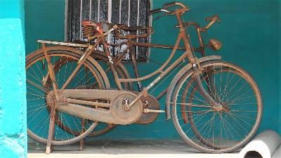 Vieux vélos rouillés sur mur bleu