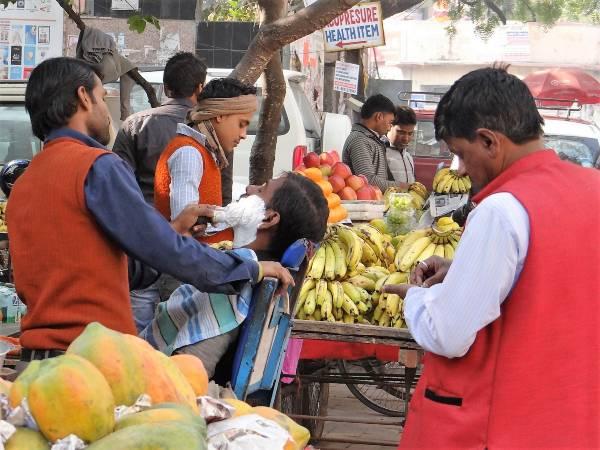 Inde barbier en action au milieu d'un stand de bananes