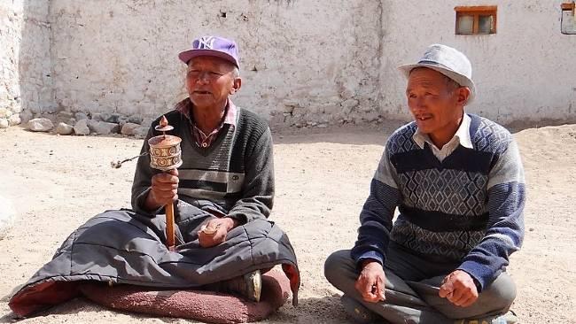 Ladakh 2 hommes assis par terre. Un tient un moulin à prières