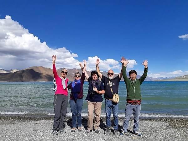 Ladakh 5 personnes lèvent les bras devant un lac