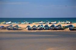 Rangée de barques sur sable avec mer en fond d'image