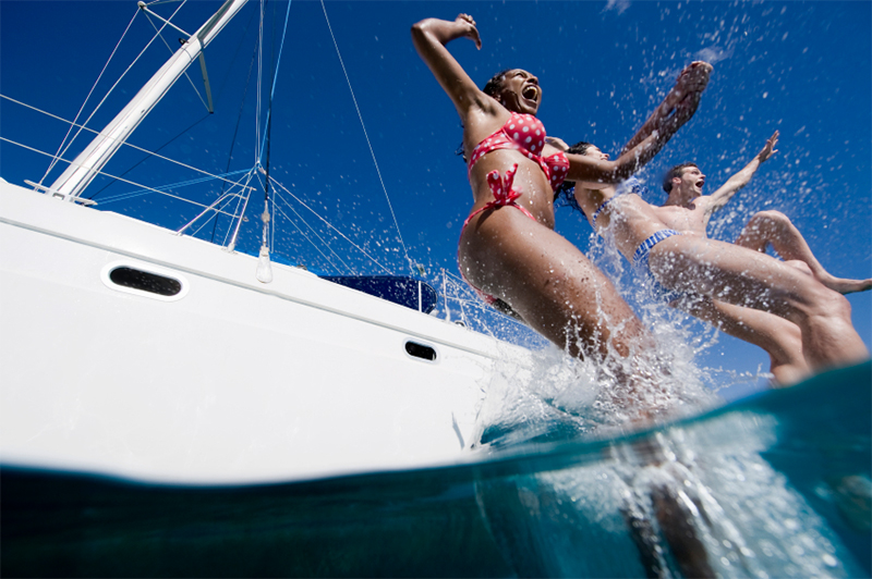 People jumping off a yacht into the ocean