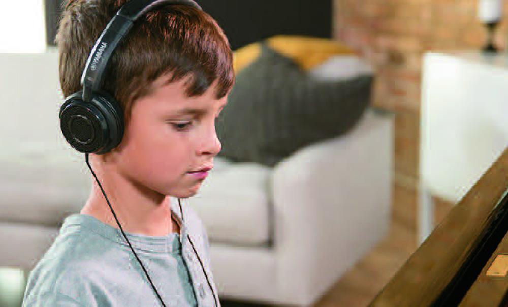 Boy playing Enspire piano silently using headphones