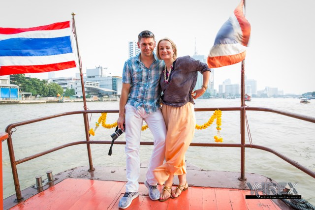 A photograph of a couple standing on a boat with Thai flags and Bangkok in background. Yarex photography Bangkok, Thailand.