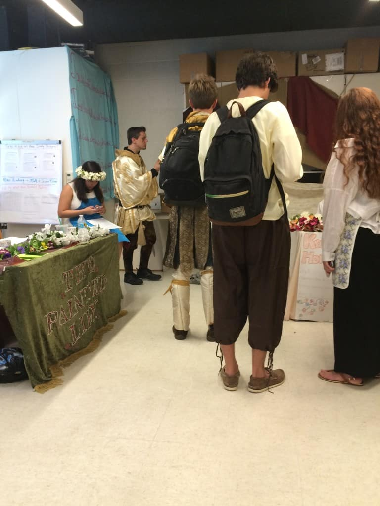 An English  teacher (on the left, in the knight costume) explaining the passports to a class.