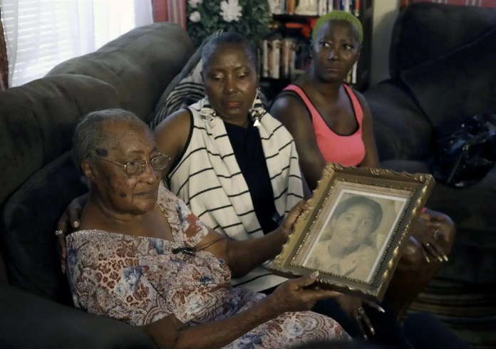 In this Aug. 23, 2017 photo, Ruby Williams, from left, holds a photo of her daughter Brenda, as she sits with her other daughters Sharon Scott and Sheila Williams in Tampa, Fla. After decades of waiting to know what happened to their relative, Tampa Police officials told the family that they found a DNA match in a jawbone found in 1986. Brenda Williams, a young mother of two, went missing in 1978. (AP Photo/Chris O'Meara)