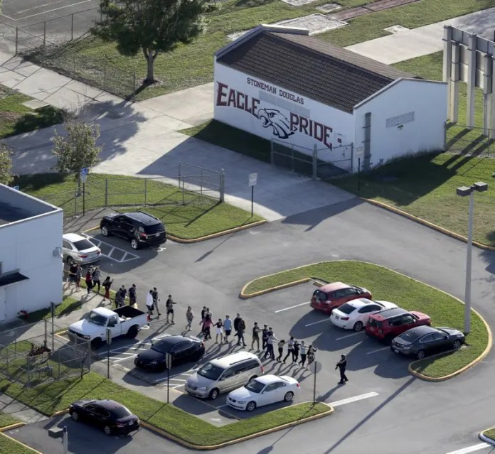 FILE - In this Wednesday, Feb. 14, 2018 file photo, students are evacuated by police from Marjory Stoneman Douglas High School in Parkland, Fla., after a shooter opened fire on the campus. It was the final period of the day at Marjory Stoneman Douglas High and Jonathan Blank was in history class, learning about the Holocaust. Across campus five of his friends, pals since grade school, sat in different classrooms watching the clock, when a former student opened fire at the school, killing more than a dozen people and injuring others Wednesday afternoon. (Mike Stocker/South Florida Sun-Sentinel via AP, File)