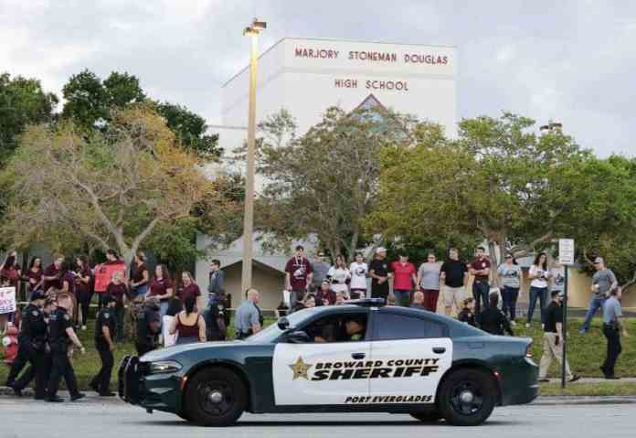 In this Feb. 28, 2018 file photo, a police car drives near Marjory Stoneman Douglas High School in Parkland, Fla., as students return to class for the first time since a former student opened fire there with an assault weapon. Calls to encourage school districts to add more armed teachers and officers have intensified since the shooting rampage at this school that left 17 students and educators dead. (AP Photo/Terry Renna)