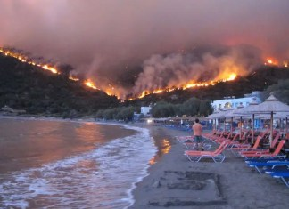 Wildfire in the island of Chios. Citizens of the village of Lithi find refuge at the beach as a wildfire burns on a mountain next to it, in the island of Chios, Greece, 18 August 2012. EPA/ALEXANDROS VLACHOS