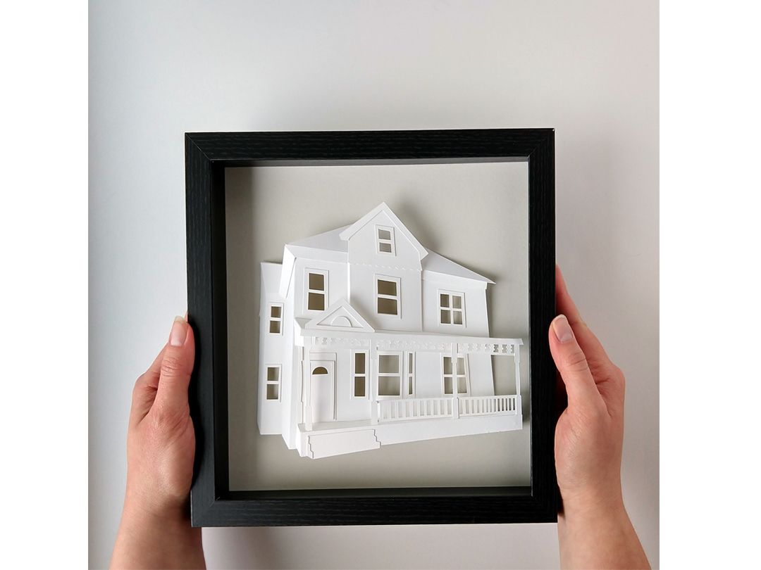 Hands holding a framed custom architectural portait