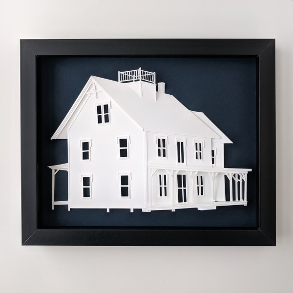 Completed paper portrait of the Maine vacation home on a navy background in a black frame