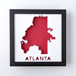 Framed map of Atlanta, Georgia cut out of white paper to reveal the red background