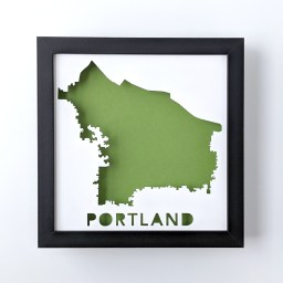 Framed map of Portland, Oregon cut from white paper to reveal a green background
