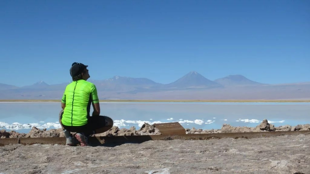 Bike packing in Chile, cycling adventure in Chile, Markus crouches next to a lake